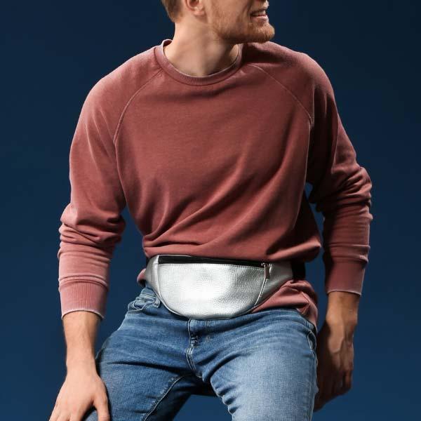 Hombre con una riñonera atada a la cintura sentando en un banco - Categoría riñoneras para hombre.
