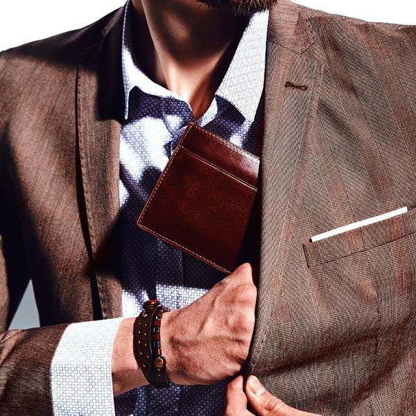 Hombre guardando una bonita cartera de piel marrón en el bolsillo de la americana - Categoría de carteras para hombre.
