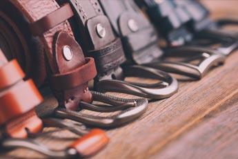 Cinturón masculino de piel enrollado con hebilla sobre el suelo - Categoría de cinturones masculinos.