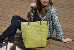 Mujer sentada en un suelo de madera sujetando un bolso shopper cogido de su asa en una de las manos