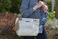 Mujer de pie en un jardín sujetando un bolso tote en el ante brazo - Categoría de bolsos Tote.