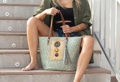 Mujer sentada en un escalón con un bolso de rafia entre las piernas - Categoría bolsos de verano.