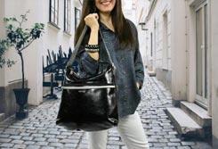 Mujer de pie en una calle sujetando un bolso de hombro negro - Categoría Bolsos de Hombro.