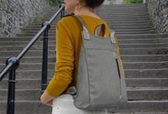 Mujer llevando una mochia de color gris delante de una escalera - Categoría mochilas de mujer